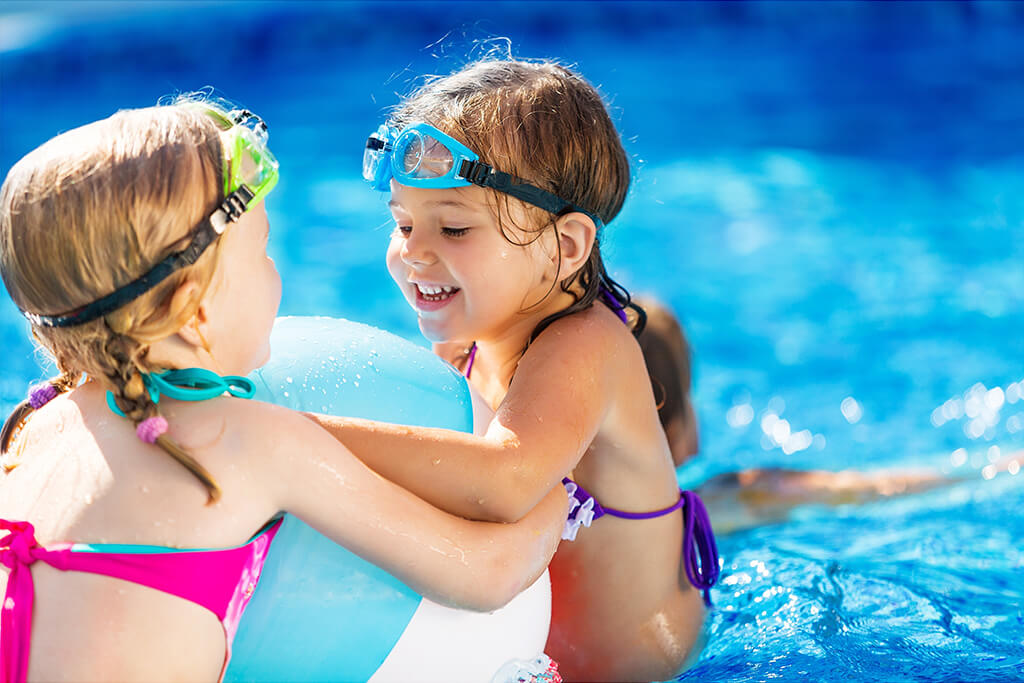 Two neighborhood children playing in the community swimming pool
